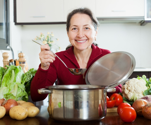 Happy mature woman cooking soup