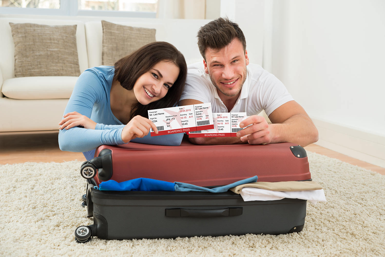 Portrait Of Happy Young Couple Packing Luggage Showing Boarding Pass