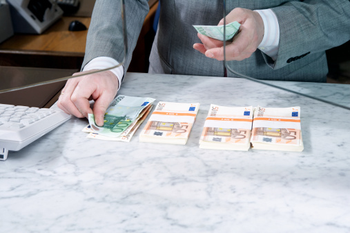 Bank teller counting Euro notes, mid section