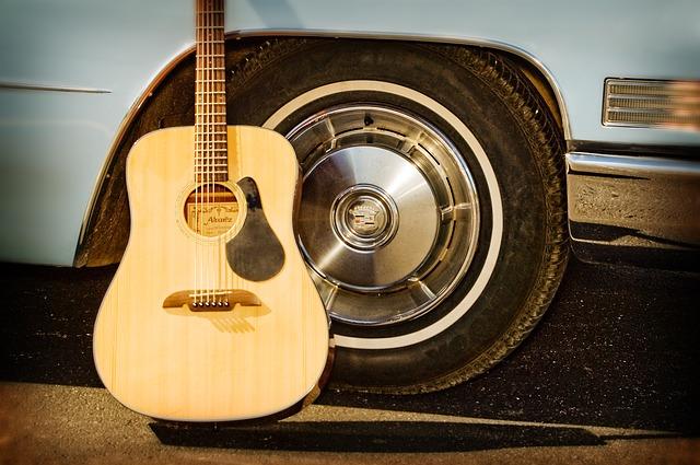 Guitare folk contre roue voiture